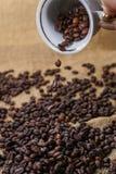 Spill ut av kaffebönor från koppen Arkivfoton