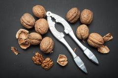 Spilld valnötter och nötknäppare på en svart bakgrund Organisk protein och omega 3 royaltyfri bild