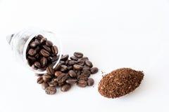 Spillda kaffebönor, kaffepulver på skeden Arkivfoton