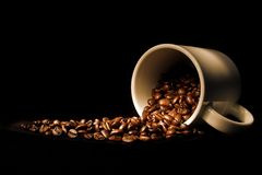 Spilled beans. Coffee cup and spilled coffee beans Stock Images