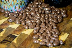 Spilled the Beans Chocolate Covered Espresso Beans with Coffee Mug up close. Chocolate Covered Coffee Beans on a solid wood cutting board in the kitchen with a royalty free stock photos