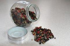 spilled black pepper on background, jar with spice Stock Images
