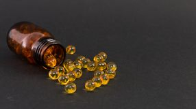 Spilled capsules of vitamine. Spilled yellow transparent golden capsules of vitamine on dark background as skin treatment concept Stock Photo