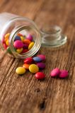 Spilled chocolate smarties around glass jar Royalty Free Stock Images