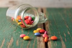 Spilled chocolate smarties on green wooden board Stock Photos