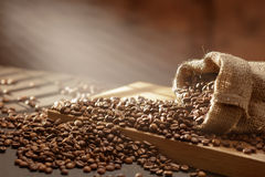 Spilled coffee beans in bag on wood Stock Photography