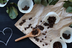 Spilled coffee beans on brown paper on a black table with hearts. Healthy food stock photo