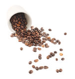 Spilled coffee beans from the cup isolated Royalty Free Stock Images