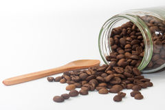 Spilled coffee beans from glass jar Stock Photography