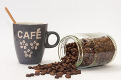 Spilled coffee beans from jar and cup with wooden spoon Stock Photos