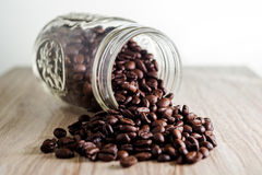 Spilled coffee beans from mason jar on wood grain texture Royalty Free Stock Photos