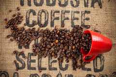Spilled coffee beans and red cup Royalty Free Stock Photos