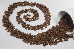 Spilled coffee beans. From the white ceramic cup a beautiful pattern on white background stock photography