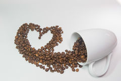 Spilled coffee beans. From the white ceramic cup a beautiful pattern on white background royalty free stock images