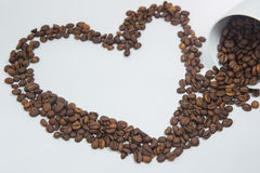 Spilled coffee beans. From the white ceramic cup a beautiful pattern on white background stock photos