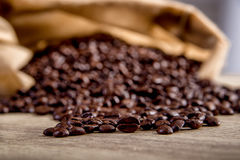 Spilled coffee beans on wooden Stock Photos
