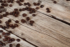 Spilled coffee beans on wooden table closeup Royalty Free Stock Photos