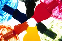 Spilled colorful paint. Paint spilled from glass bottles onto a white background and including yellow, green, red, black, blue and brown stock photography