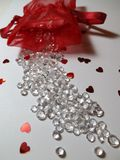 Spilled diamonds and hearts from a red lace net bag. On a white background stock photos