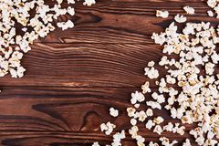 Spilled on the edges of popcorn on a wooden brown background Stock Photography