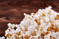 Spilled on the edges of popcorn on a wooden brown background Royalty Free Stock Images