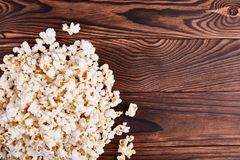 Spilled on the edges of popcorn on a wooden brown background Royalty Free Stock Image