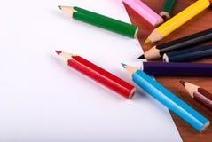 Spilled färbte Bleistifte und Weißbuch auf Schreibtisch Stockbilder
