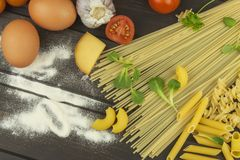 Spilled flour. Pasta and vegetables on a wooden table Stock Image