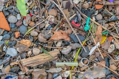 Spilled garbage on the beach of the big city. The accumulation of plastic objects in the Earth`s environment adversely affects stock photos