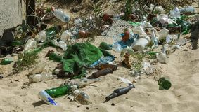 Spilled garbage on beach of big city. Empty used dirty plastic bottles. Dirty sea sandy shore Black Sea. Environmental pollution. Ecological problem.  Garbage Stock Photography