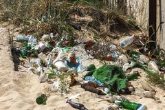 Spilled garbage on beach of big city. Empty used dirty plastic bottles. Dirty sea sandy shore Black Sea. Environmental pollution. Ecological problem.  Garbage Royalty Free Stock Photo