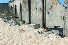 Spilled garbage on beach of big city. Empty used dirty plastic bottles. Dirty sea sandy shore Black Sea. Environmental pollution. Ecological problem.  Garbage Royalty Free Stock Photos