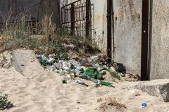 Spilled garbage on beach of big city. Empty used dirty plastic bottles. Dirty sea sandy shore Black Sea. Environmental pollution. Ecological problem.  Garbage Stock Images