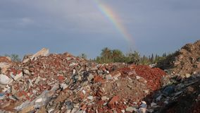 Spilled garbage and colorful rainbow at blue sky. Environmental pollution. Ecological problem. Concept ecology