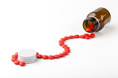 Spilled from a glass apothecary bottle red pills Stock Images