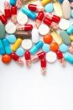Spilled ha colorato le capsule e le pillole della medicina sulla superficie bianca Immagine Stock