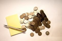 Yellow notebook with pen and mountain of mettalical coins on white background. Spilled iron coins next to yellow blank sheets of paper and ballpoint pen, on stock image