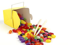 Spilled Jellybeans. Colorful jellybeans spilling from a yellow takeout container Stock Photo