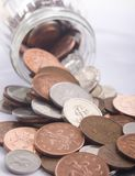 Spilled Money. Selection of various UK Sterling coins spilling out of a money jar, ideal for a business or finance background. Please see all my other money / Royalty Free Stock Photo