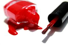 Spilled nail polish enamel red with brush and bottle on white background Royalty Free Stock Photo