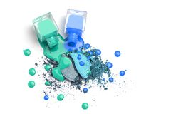 Spilled nail polishes bottles on blue eye shadows cosmetic. Isolated on white. Creative cosmetic concept royalty free stock image