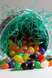 Spilled pail of jelly beans. Easter pail lying on its side with easter grass and colorful jelly beans spilling out of it Royalty Free Stock Images