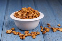 Spilled peanuts by a bowl. A studio image of roasted peanuts in a dish with some spilling over Royalty Free Stock Photography