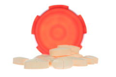 Spilled Pills. A photo of some pills piled in front of their container set against a white background royalty free stock image