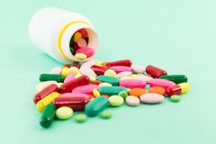 Spilled pills or tablets out of a bottle. On green medical table Stock Image