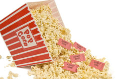 Spilled Popcorn and Movie Tickets. Popcorn and movie tickets spill out of a red and white striped popcorn container Royalty Free Stock Photography