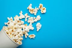 Spilled popcorn from a paper bucket or a cup on a blue background.  stock photography