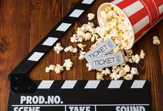 Spilled popcorn, striped box, movie tickets and movie clapper ag. Ainst the dark wood Royalty Free Stock Images