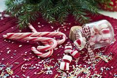 Christmas sweet candies spilled/poured from glass. Spilled/poured from glass jar sweet candies with red and white candy cane on red christmas background Royalty Free Stock Photography