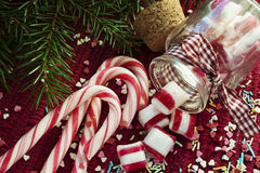 Christmas sweet candies spilled/poured from glass. Spilled/poured from glass jar sweet candies with red and white candy cane on red christmas backround Stock Photography